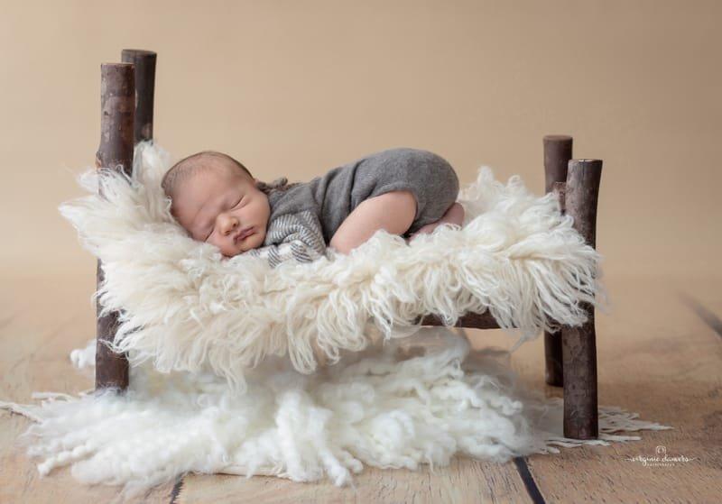 Bébé 8 jours pose sur lit en bois