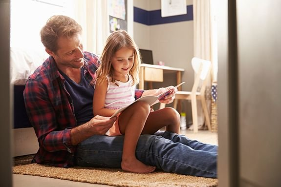 Father and daughter reading a PJ Library book together.