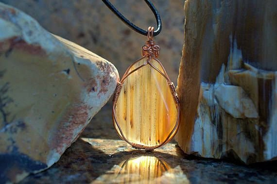 yellow color gemstone pendant with reddish stripes
