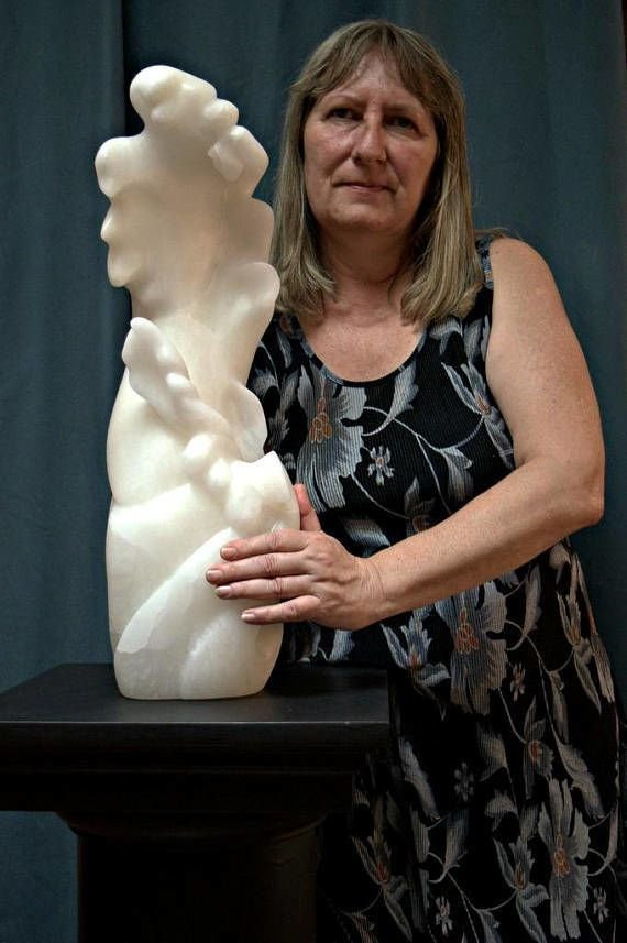 tall white abstract sculpture on a stand with the female artist holding it