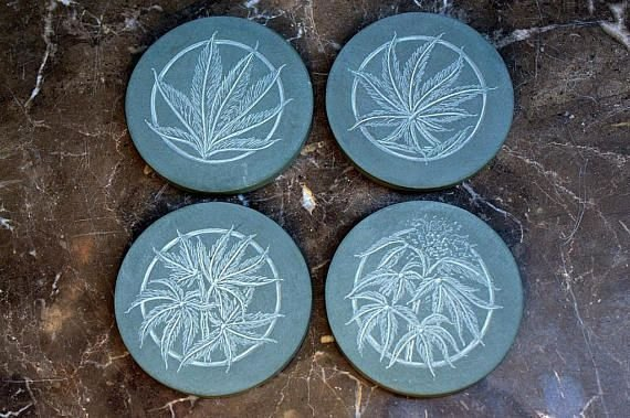 four different Cannabis leaf carving on green disc shape stone