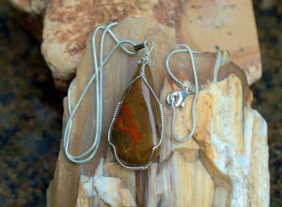 brown stone with red spotty pattern in silver wire setting