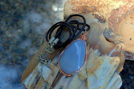 aqua blue gemstone with copper wire on raw rock