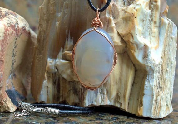 translucent peach coloer gemstone in cooper wire wrapping
