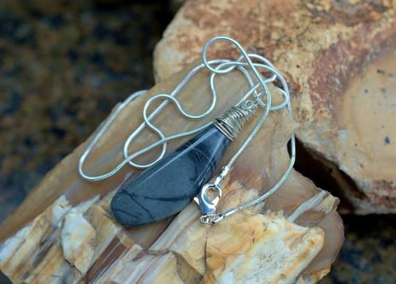 gray stone pendant with black abstract style pattern