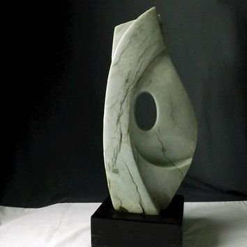 Abstract stone sculpture wave shape with hole in the middle on a black square base stone