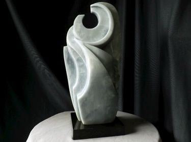 Abstract stone sculpture sitting bird shape with open hole on top