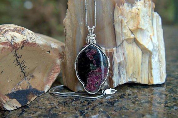 black oval shape crystal with violet pattern