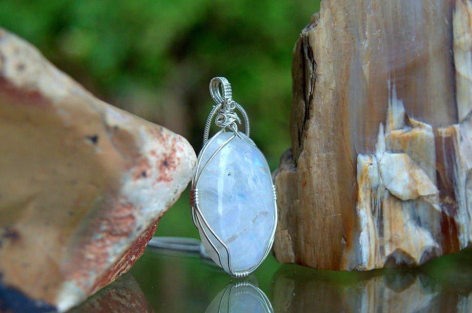 white shimmering blue flash gemstone in silver setting