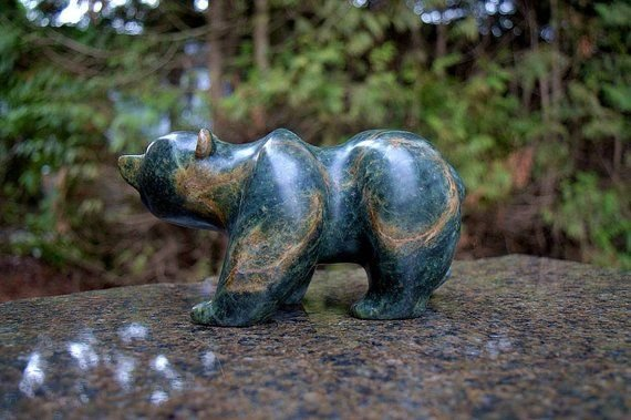 green walking stone bear with trees in background