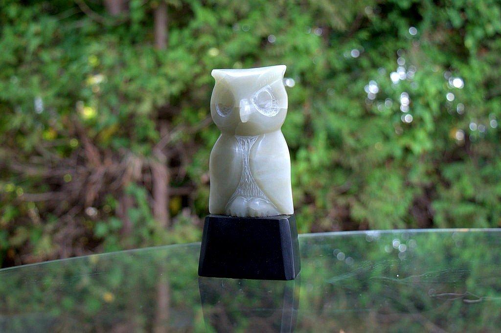 green stone owl figurine on black stone base