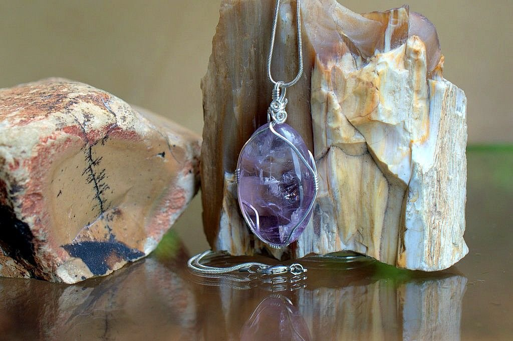 large purple crystal pendant in silver wire setting