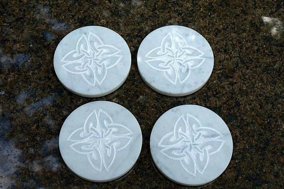 white round marble coasters with carved design