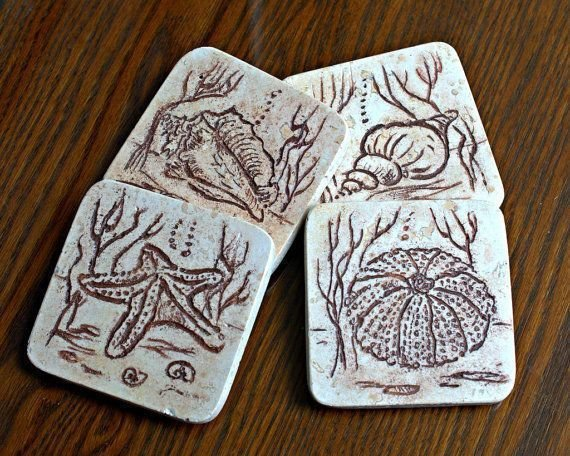 beige stone coasters with marine animals carving