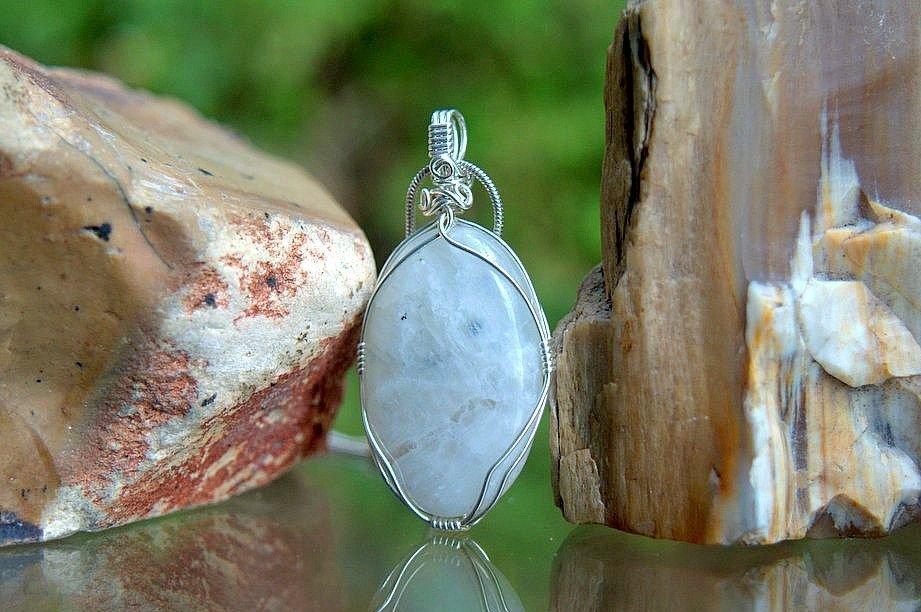 white gemstone pendant with blue flash