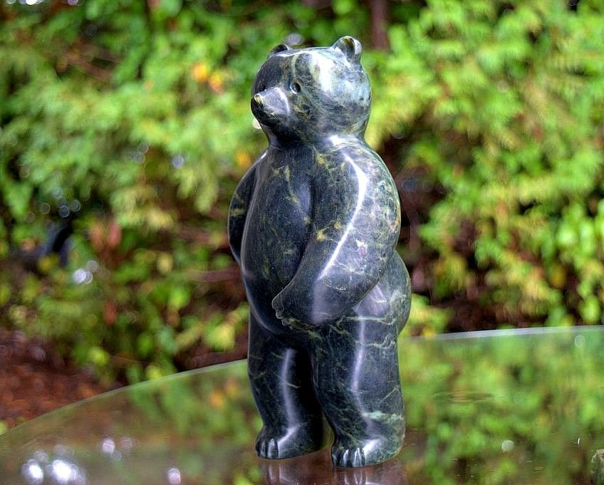 green stone bear walking on two legs sculpture