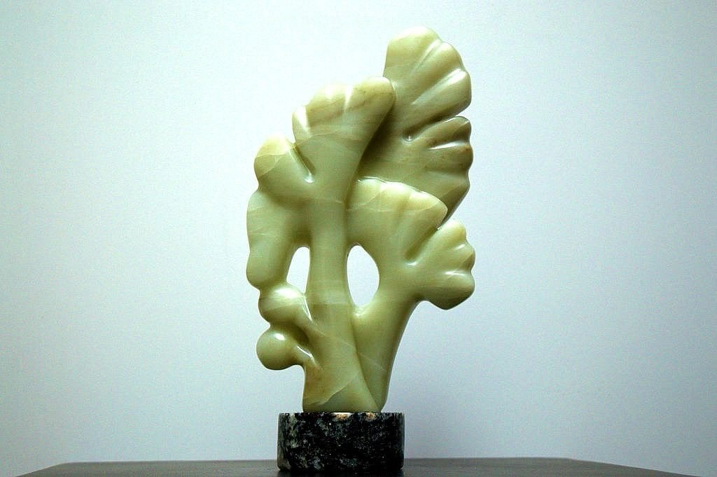 green tree branch stone sculpture on round black base