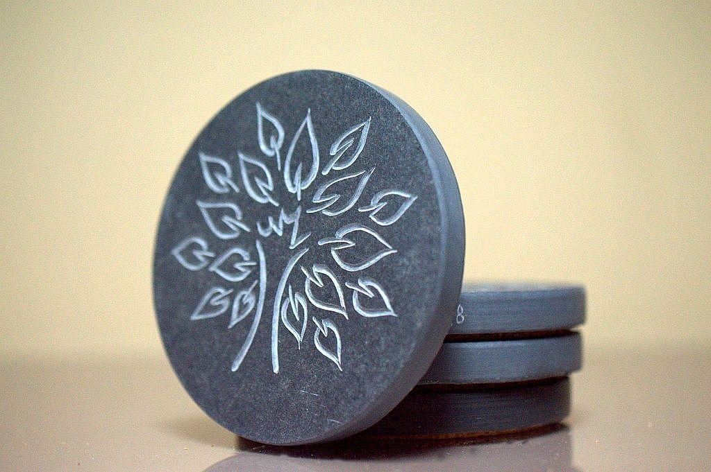 tree fantasy carving on black disc shape stone