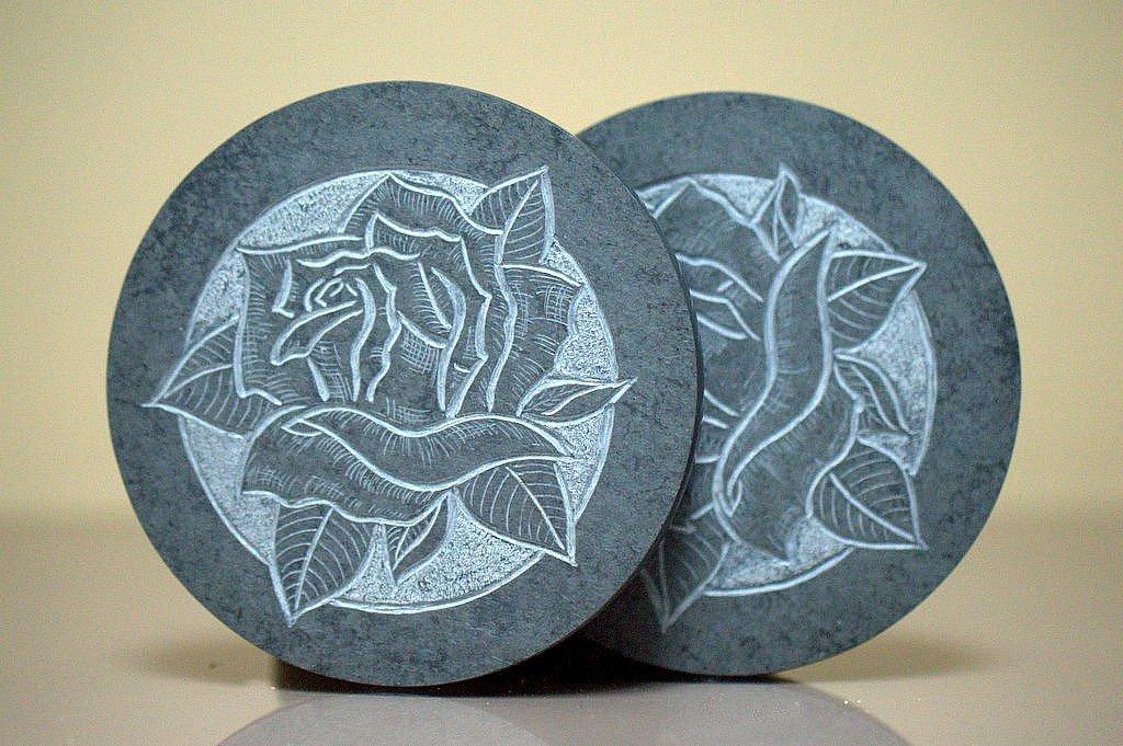 hand carved rose design on black round stone