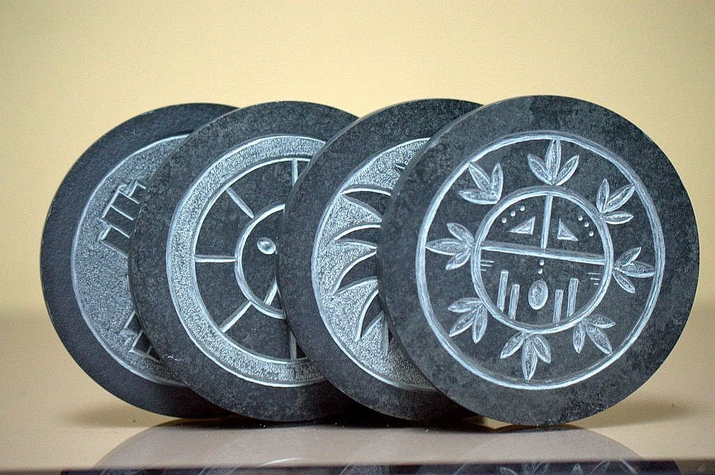 four black round shape carved stone drink coaster