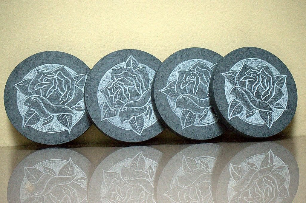 four black round shape drink coaster with rose carving