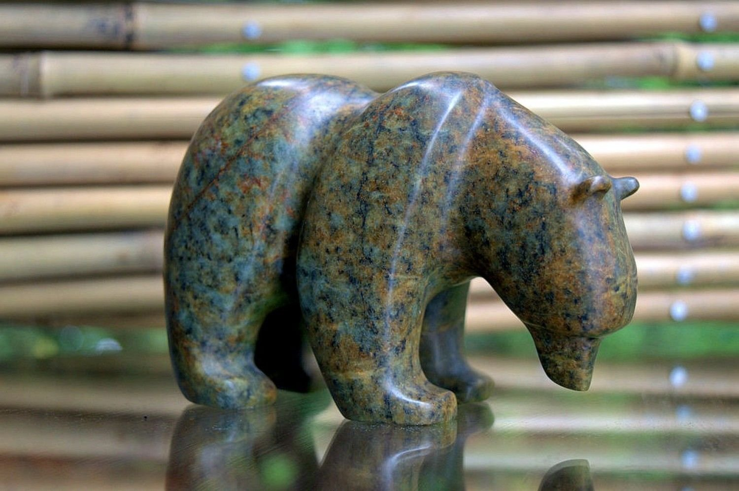 bowed head green brown stone bear carving