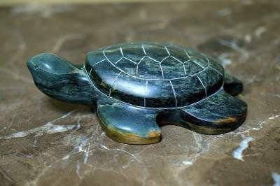 deep green turtle stone figurine on brown marble