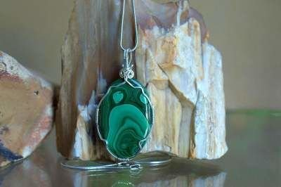 green oval shape mineral pendant with swirly pattern