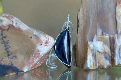 shimmering blue gemstone pendant with silver setting