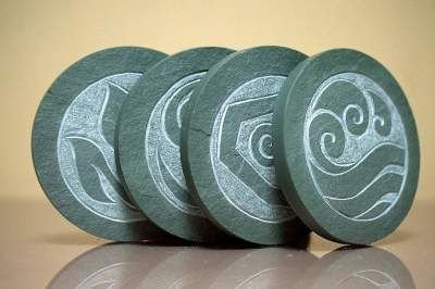green carved stone stone with the four elements symbol