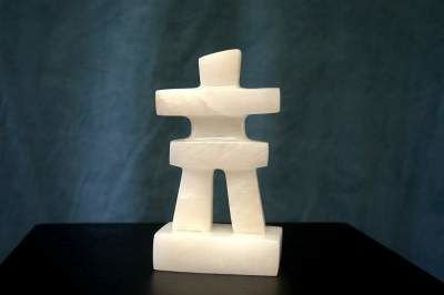white stone human figurine with spread arms