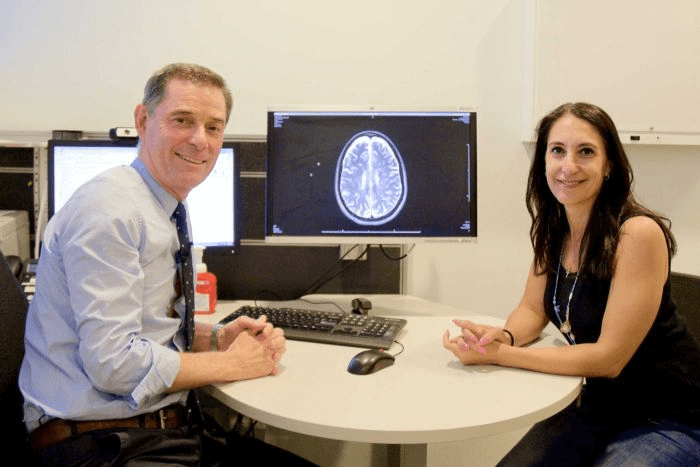 Dr Moore with Ms Zorbalas, with a brain scan in the background.