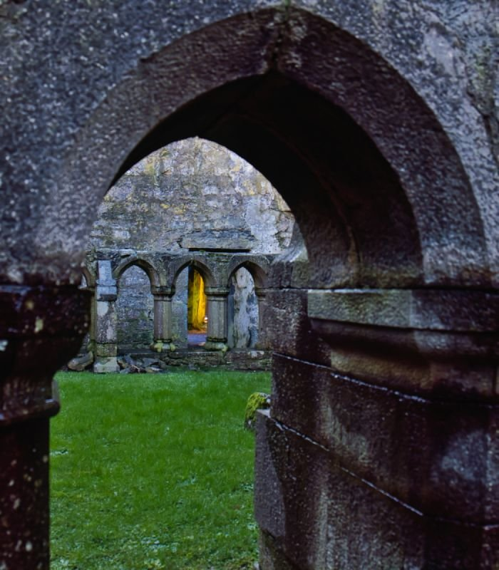 A sunlit doorway through the cloisters at Ross Errilly Friary