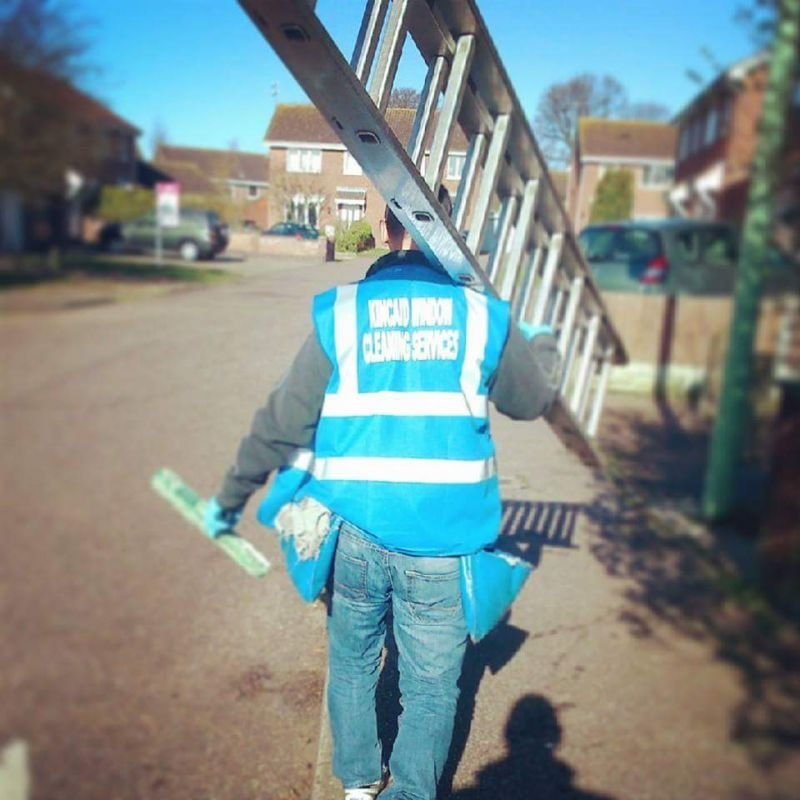 Rob going to clean windows in Lowestoft with ladder on his shoulder.