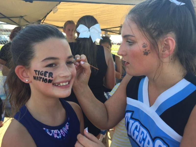 Cheerleaders face paint during Night at the Ike